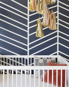 Taped and painted wall to make an organic chevron. Love how it matches the pillows (even though p.s. read the baby books - NEVER put anything in a crib with a baby, not even aesthetic pillows!).