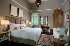 For a guest room in his Singapore bungalow, Michael Fiebrich designed the bleached-teak bedside tables, blown-glass-and-nickel lamps, and charcoal nude studies. Contrasting chair rail molding in the same hue as the ceiling gives the appearance of height.