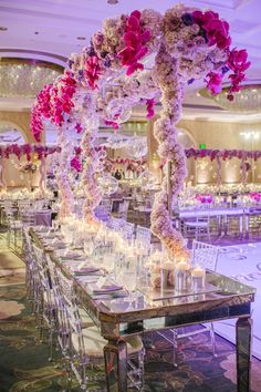 High above the mirror guest table, gleaming metal scaffolding held arrangements of purple roses, fuchsia orchids, and ivory hydrangeas. (📷: Joe Latter Photographer) Lavender Centerpieces, Wedding Reception Centerpieces, Floral Centerpieces, Wedding Decorations, Flower Arrangements, Tall Centerpiece, Table Arrangements, Wedding Receptions, Reception Ideas