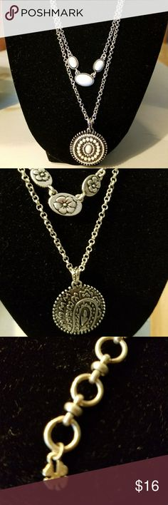 SILVER LUCKY BRAND REVERSIBLE NECKLACE. Medallion has white lacquered pearl like design on one side and the other is a floral carved design. The end of the chain has the signature Luck 4 leaf clover. GUC Lucky Brand Jewelry Necklaces