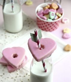 """Upgrade plain old milk and cookies with this on-target idea. Create a hole in a heart-shaped cookie. Place the cookie on top of a milk glass, then insert a paper straw """"arrow"""" embellished with construction paper fringe."""