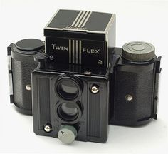 Another distinctive design from Universal Camera Corporation, the Twinflex is a small twin-lens reflex camera made of bakelite and aluminum. The knob at the bottom provides focus for both lenses by moving the front of the camera in and out, making it a true TLR. I was very happy to have won the auction for this, as it's been on my wish list for a long time. This one is in excellent condition, and came with its original box (complete and in great shape) and instruction booklet. The Twinflex…
