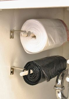 Organize Your Kitchen (On a Budget!)- curtain rod holders & dowels holding trash bags out of sight & easy to reach