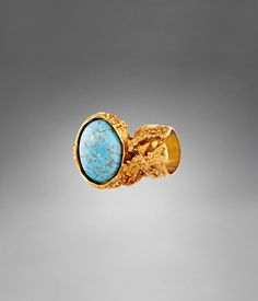 YSL Arty Oval Ring with Turquoise Stone $250    A symbol of bohemian, Rive Gauche-chic and outspoken sophistication, this Iconic Arty ring pays homage to the renowned Yves Saint Laurent couture jewelry collection. A textured gold-finish metal setting encases a brilliant stone - a true statement piece that moves effortlessly from day to evening.