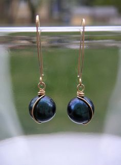 Dark Blue Pearl Earrings Small Gold Dangles ~ A modern take on the classic pearl drop earring. Dark blue fresh water pearls are wire wrapped in an elegant twist of 14k gold fill wire and dangle on custom hand shaped and hammered ear wires. Pearls, the birthstone for June, are said to