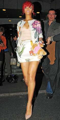 Rihanna brings a touch of spring to a fall day, pairing her floral ensemble with bright pink lips and nails while out and about in London on Tuesday.