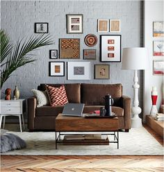 example of how to decorate around a dark sofa. The gallery style art, the pale gray walls, and the airy furniture accents combine to balance the visual weight of a dark sofa anchored in the center of the space Couches Living Room, New Living Room, Living Room Grey, Trendy Living Rooms, Apartment Living Room, Living Room Inspiration, Brown Sofa Living Room, Living Room Sofa, Room Inspiration