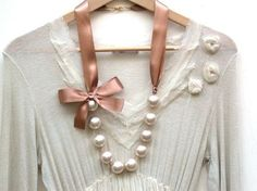 ribbon is brown but could do whatever. Pearls strung with loops not through knotted ribbon