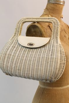 Adorable wicker bag! Done in a white wicker with flap and turnlock. Vinyl interior with side pocket. Leather tabs on the bottoms with gold stud