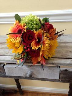 Mixed rustic fall bouquet of red garden roses, sunflowers, green hydrangea, gerbera daisies
