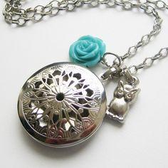 Delicado colar prateado com um relicário vazado redondo e mais dois pingentes, uma pequena e delicada rosa azul e uma corujinha.