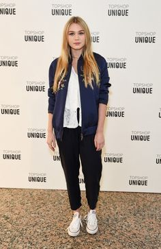 Immy Waterhouse wears a lace top, embroidered bomber jacket, cropped trousers, and Converse sneakers