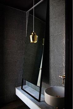 Un moderno aseo en negro, gris y blanco con una lámpara colgante dorada como la grifería.