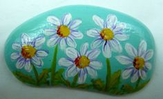 Hand Painted Rock with the Design of a Bunching of Daises with a Sky Blue Background and green leaves and Purple Details on the Flowers