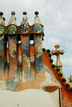 The roof terrace is one of the most popular features of the Casa Batlló due to its famous dragon back design. Antoni Gaudí represents an animal's spine by using tiles of different colors on one side. The roof is decorated with four chimney stacks, that are designed to prevent back draughts. Barcelona, Catalonia. Photo Chang Min Yun