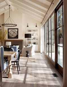 Custom-stained oak hardwood flooring and white-washed exposed beams overhead lend a rustic ambiance throughout the main living space.