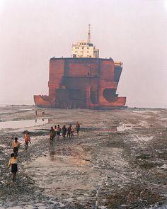 La realidad supera en este caso a la ficción. En las playas cercanas a la ciudad de Chittagong, Bangladesh, miles de personas mal viven desguazando barcos. Estos son varados con la intención de ahorrar costes. La contaminación y la suciedad saltan a la vista.  alexiuss.deviantart.com