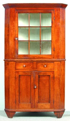 """Sold For $4,750 Somerset County, Pennsylvania Country Federal Tiger Maple Two Part Corner Cupboard. Tapered cornice above a single nine-pane glazed upper door, two split dovetailed drawers, two lower paneled doors and continuous bracket feet. Condition: Old refinish one glass pane with crack and normal wear. 84 ¼""""h x 48""""w x 20""""d."""