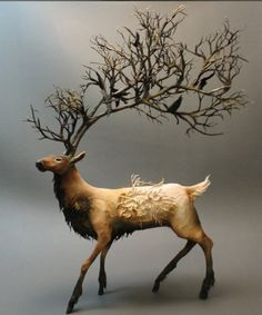 deer with antler branches and bird sculpture