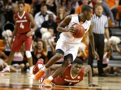 Oklahoma State's Jawun Evans (1) goes past Arkansas' Trey Thompson (1) during an NCAA college basketball game between Oklahoma State University (OSU) and Arkansas at Gallagher-Iba Arena in Stillwater, Okla., Saturday, Jan. 28, 2017. Photo by Bryan Terry, The Oklahoman