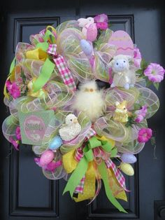 I call this fun Easter deco mesh door wreath Easter Friends because it has a fuzzy yellow chick in the center as well as a plush baby lamb, baby duck and yellow glittered bunnies. A 5 x 5 Happy Easter sign also adorns the wreath. Pastel yellow, green, blue and pink stripes is the pattern of the foil mesh. A large metal pink patterned Easter egg as well as many pastel foam Easter eggs are interspersed around the wreath. Pink silk petunias add a lovely touch to this Easter door wreath. Four…