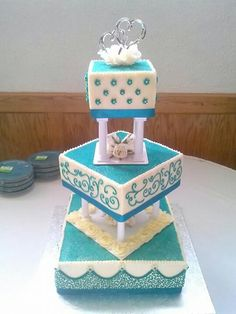 Teal tierred square wedding cake with pillars