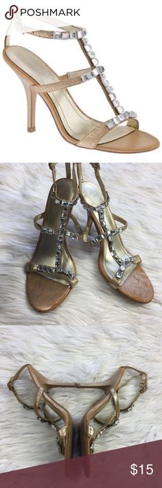 •• BCBG Luxx Heels • Rhinestone T-Strap Sandals Super cute gold t-strap BCBG heels. Beautiful shoes in good used condition overall. Worn and well loved. Does have one gem missing but it's not noticeable at all during wear due to setting being the same color. The bling you gems against the gold body really make them stand out. Looks really great with dresses or even jeans and a t-shirt.  Comes from a pet free smoke free home. (LLR0-0595) BCBG Shoes Heels