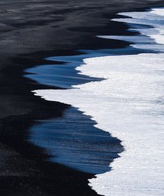 Waves lap the black sand at Dyrholaey Beach, Iceland. The sand at Dyrholaey Beach is composed of black volcanic ash and lava. #beaches #iceland Photo credit: © David Elliott