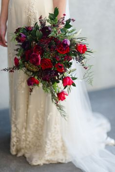 Red wedding bouquets are more than just round bouquets of red roses. Embrace the loose, organic look that has become so popular in the last few years. This bouquet almost looks like it was arranged from flowers picked in a garden and includes flowers like roses and tulips, but even tiny wildflowers. | Gorgeous Red Wedding Bouquets