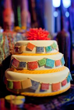 Tiered cake with Mexican crepe paper flag motif. Day of the Dead.
