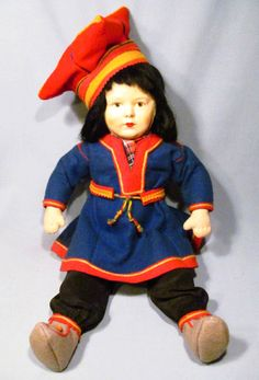 "Fabulous old Ronnaug Petterssen Sami boy doll. He is all cloth with a beautiful hand-painted face. His Laplander costume is all original and finely crafted. He measures 15"" tall (18"" to the top of his hat) and is in excellent condition."
