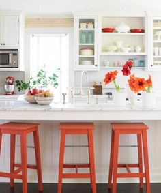 Sometimes a colorful accent is all that's needed to take an island from pretty to peppy. Red barstools wow this country-style island, defined by flat-board paneling on the island base, marble countertops and a country-style bridge faucet.