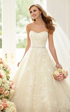 This strapless Stella York lace and Regency Organza ball gown wedding dress features a semi-sweetheart neckline, chapel train, and Diamante-encrusted waist belt. The back zips up under fabric-covered buttons.
