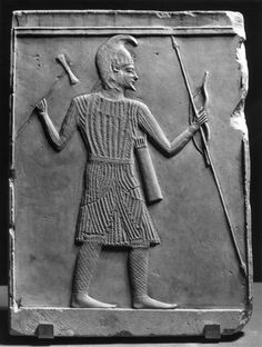 Scythian Warrior with Axe, Bow and Spear Greek 4th-2nd Century BC This flat relief depicts a Scythian warrior with an axe, bow, and spear. There are red designs in the background. All the edges are complete. There is a tongue pattern at the top. Source: The Walters Art Museum