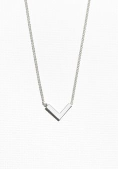 An edgy brass necklace featuring a delicate chain and an arrow pendant.