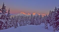 Alpenglow warming the summits of the Three Sisters and Broken Top Mountain as viewed from Central Oregon's Tumalo Mountain.