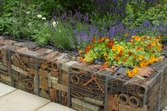 Gabion walls of recycled terracotta pots is featured in The Real Rubbish Garden by Claire Whitehouse, an environmentally friendly garden with recycled household materials, at The Chelsea Flower Show 2005 in London.