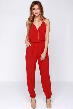 """Even if you're too timid for skydiving, the Learning to Fly Red Jumpsuit will take you on an unexpected journey! This woven jumpsuit is as fun as it is cute, adding adjustable halter ties to a sexy wrap bodice, plus a strip of elastic at back for fit. Cinched waist has hidden elastic, and pocketed pants billow into elastic ankle cuffs. Unlined. Model is 5'7"""" and is wearing a size X-small. 100% Rayon. Hand Wash Cold or Dry Clean. Made with Love in the U.S.A."""