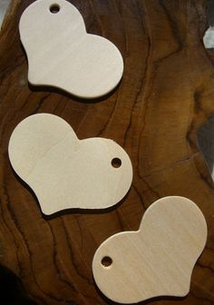 """Wood Heart Shaped Tags (2-5/8""""). My father lovingly burned J + A into 50 of these hearts and we used raffia to tie them from the grape vines on the ceiling."""