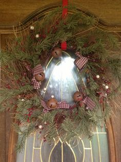 "Such a pretty wreath...Rustic pine wreath with bells and stars, homespun ribbon. 24"" and is $39.99  Primitivehomrdecorandmore.com"