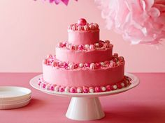 The secret ingredient for Ina Garten's moist cake layers? The addition of sour cream. Bake a 9-inch, a 6-inch and a 3-inch layer and frost each separately with hot-pink icing. Chill each frosted layer before stacking, then pipe or spoon the remaining frosting around the base of each cake and around the top edge of the top layer before finishing with candy decorations.