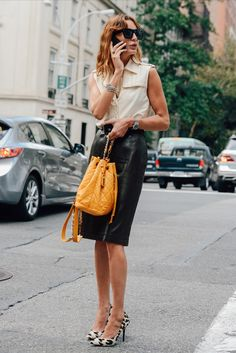 Shop this look for $148:  http://lookastic.com/women/looks/pencil-skirt-and-crossbody-bag-and-pumps-and-watch-and-sleeveless-button-down-shirt-and-sunglasses/3681  — Black Leather Pencil Skirt  — Mustard Leather Crossbody Bag  — White Leopard Suede Pumps  — Silver Watch  — Beige Sleeveless Button Down Shirt  — Black Sunglasses