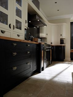 Rounded top cabinets, black stained lower cabinets both with attractive hardware, big tiles on floor. Milton Charcoal