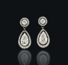 A PAIR OF EARLY 20TH CENTURY DIAMOND EAR PENDANTS Each circular-cut diamond top within a millegrain-set diamond line surround, suspending a single old-cut pear shaped diamond drop and similar frame setting, circa 1910