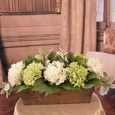 This is a perfect design for a dining table, kitchen island or coffee table. Designed from realistic looking white and green silk hydrangeas with dainty petals accented with lambs ear and succulents.   Set in a wooden planter for a casual farmhouse style. 11'' H x 11'' W x 20'' D Sunflower Floral Arrangements, Artificial Hydrangeas, Clear Glass Vases, Wooden Planters, Decor Pillows, Allium, Flower Boxes, Silk Flowers, Flower Art