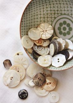 Carved Mother of Pearl Buttons spilling out of bowl.