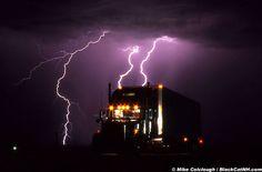 A desert thunderstorm backlights the trucker's night stop along Interstate 10 in Arizona.