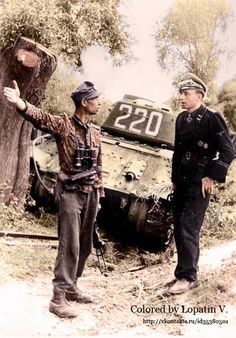 German officers conferring beside an abandoned Soviet T-34 tank.