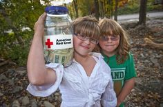 September 16, 2011. Binghamton, New York. Sisters Paige, left, and Maggie O'Brien of Greene with the jar of money they collected for the American Red Cross by selling lemonade and Whoopie pies in front of their flooded home. Paige said that people just need to put on boots and go help others clean-up from the floods.
