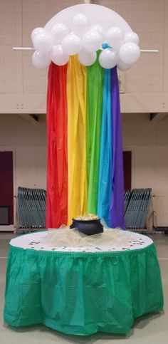 Cute & simple St. Patrick's Day party decor - rainbow made with plastic tablecloths, balloon cloud & pot of gold (favors). Designed by Pridmore Event Planning & Design.